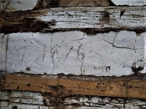 """""""1876"""" written into chinking on front of log house."""