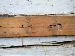 Emanuel Ruse's name was written on a nail-board on logs in front of house.